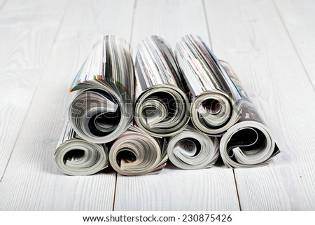 Close up of newspapers and magazine on white wood floor - stock photo