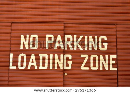 Close up of no parking loading zone on metal red door. - stock photo