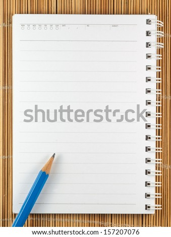 Close up of notebook with pencil on bamboo background - stock photo