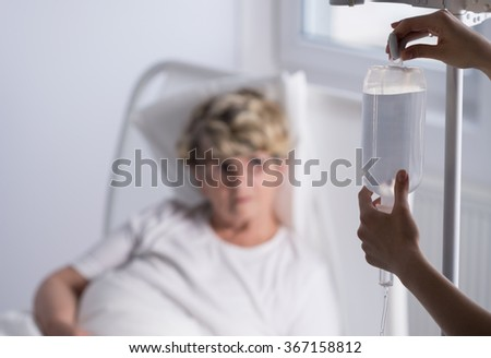 Close-up of nurse changing a drip bag - stock photo