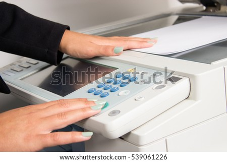 Close up of office printer and woman's hand using it.