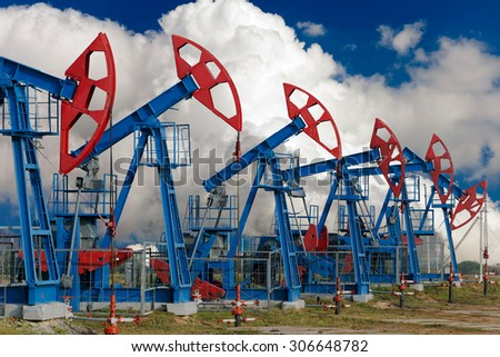 close-up of oil pumps on background of dramatic clouds at sunset - stock photo