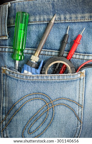 Close-up of old electric soldering iron gun with the blue handle and Roll of soldering wire and screw driver in Blue Jeans Pocket. - stock photo