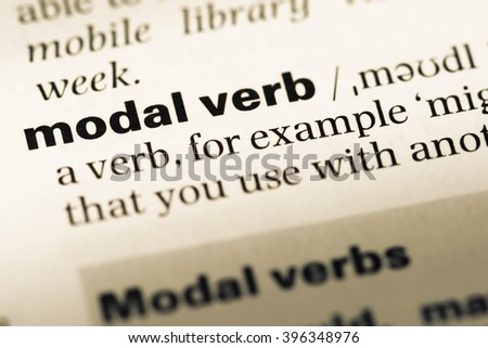 Close up of old English dictionary page with word modal verb - stock photo