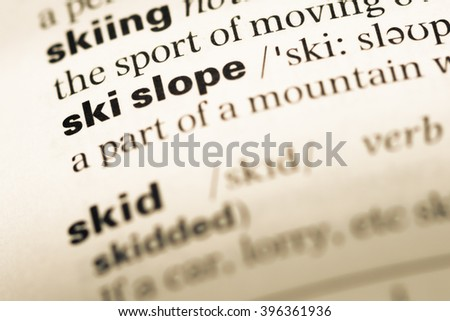 Close up of old English dictionary page with word ski slope - stock photo