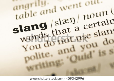 Close up of old English dictionary page with word slang - stock photo