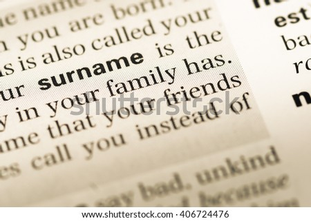 Close up of old English dictionary page with word surname - stock photo