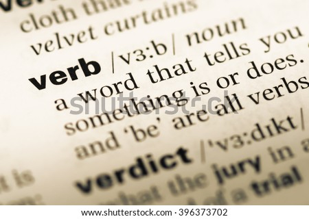 Close up of old English dictionary page with word verb - stock photo