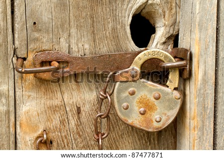 Close up of old fashioned antique lock on a worn wooden door. - stock photo