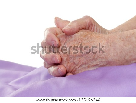 Close-up of old hands praying on the bed - stock photo