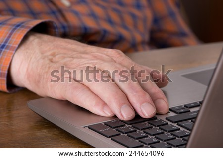 Close up of old male hand on keyboard of laptop  - stock photo