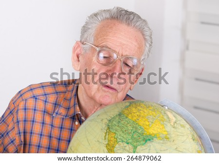 Close up of old man with reading glasses looking at globe