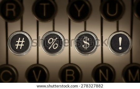 "Close up of old manual typewriter keyboard with scratched chrome keys. Focus and lighting centered on middle row containing ""#"", ""%"", ""$"", and ""!"" keys representing swearing. 