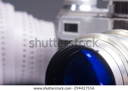 Close-up of old photo camera with a metal lens and viewfinder. A roll of 35mm movie film - stock photo