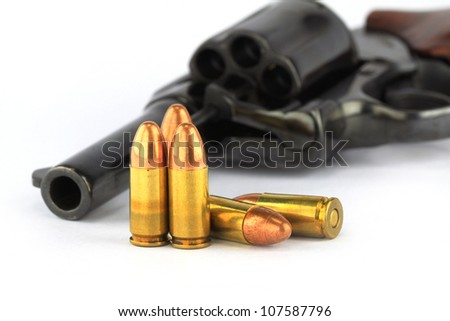 Close up of old revolver with bullets on white background - stock photo