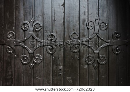 Close up of old wooden door with metal decoration - stock photo