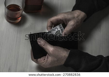 Close-up of older alcoholic man counting money - stock photo
