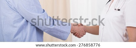 Close-up of older man and young female nurse handshake - stock photo