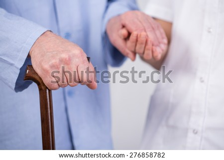 Close-up of older man's hand holding walking stick - stock photo