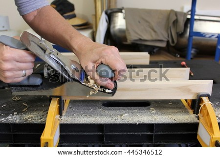 Close up of Older woman Planing timber 4 - stock photo