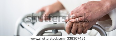 Close-up of older woman with walker and family's support - stock photo