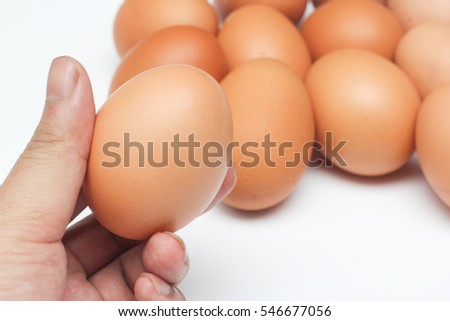 Close up of one egg that men's hand pick it up from the other eggs (isolated on white background)