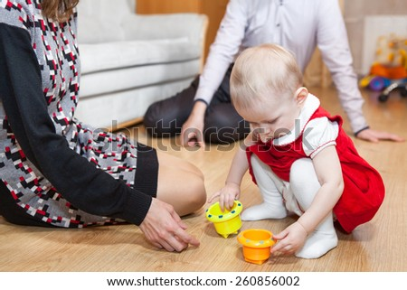 Close up of one year baby girl playing wit parents on floor - stock photo