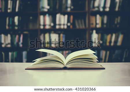 Close up of open book on desk and bookshelf with vintage filter blur background - stock photo