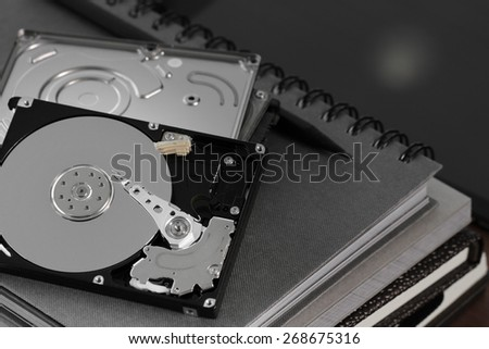 Close up of open computer hard disk drive on desk and notebook
