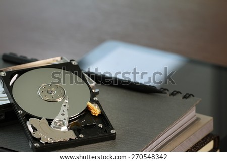 Close up of open computer hard disk drive on desk and notebook  - stock photo
