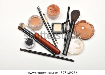 Close-up of open jar of loose powder, compact powder, eyeliner, eyebrow powder, eyeshadow makeup brushes and on white - stock photo