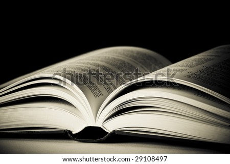 Close-up of opened old book against black background. Space for text. Shallow DOF. - stock photo