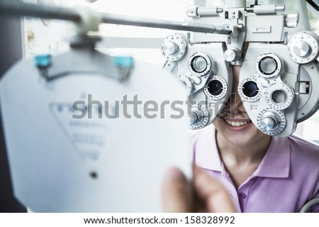 Close-up of optometrist doing eye exam on young woman - stock photo