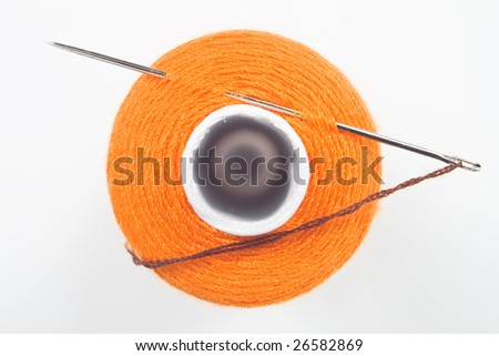 close up of orange sewing spool with a needle