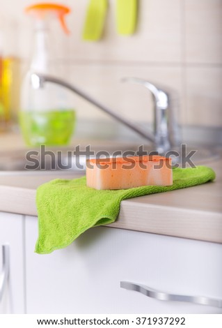 Close up of orange sponge and green cloth on the kitchen countertop. Clean sink and faucet in background - stock photo