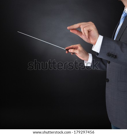 Close-up Of Orchestra Conductor Hands Holding Baton Over Black Background