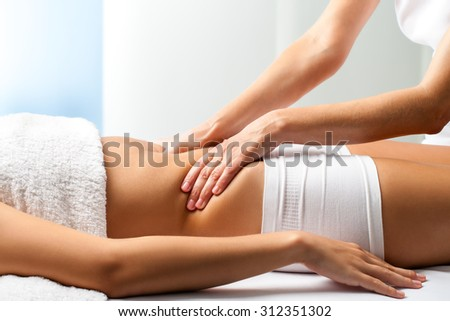 Close up of osteopath doing manipulative abdomen massage on female patient. - stock photo
