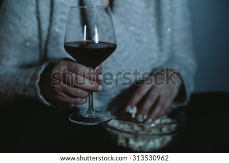Close up of overweight woman watching TV with glass of wine and popcorn - stock photo