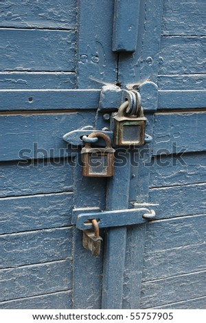 Close up of padlocks and latchs keeping wooden door closed - stock photo