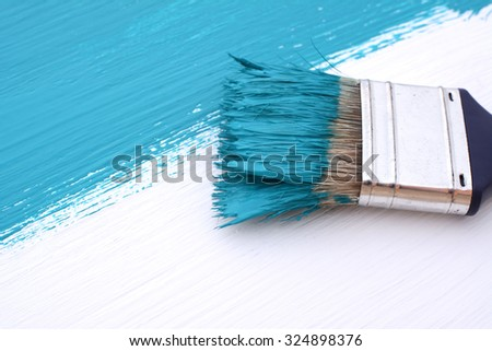 Close-up of paintbrush with paint-covered bristles painting a white board blue - stock photo