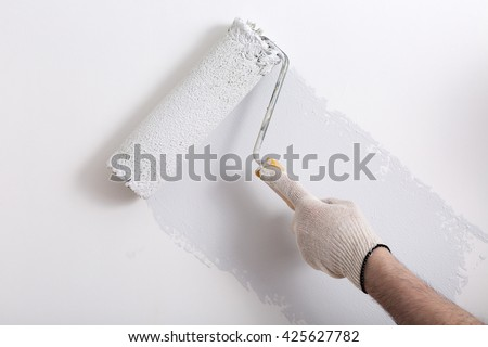 Close up of painter arm painting a wall with paint roller - stock photo