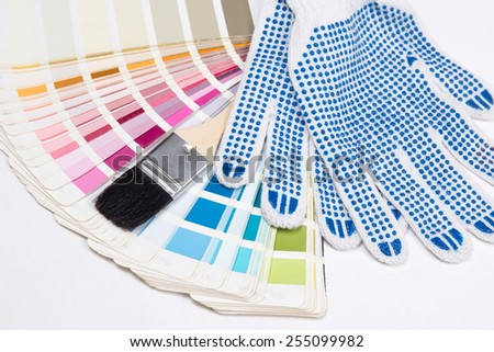 close up of painter's tools - brush, work gloves and colorful palette over white background - stock photo