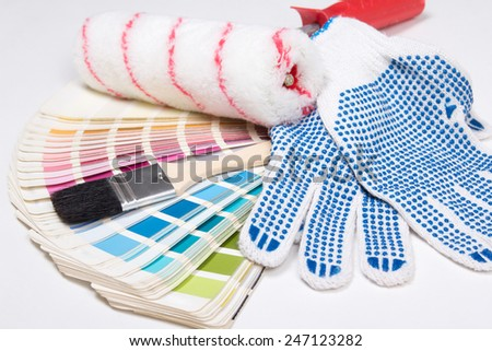 close up of painter's tools - brushes, work gloves and colorful palette over white background - stock photo