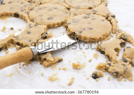 Close-up of palette knife lifting peanut butter and chocolate chip cookies from kitchen worktop - stock photo
