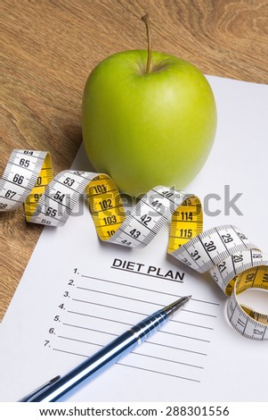 close up of paper with diet plan, pen, green apple and measure tape - stock photo