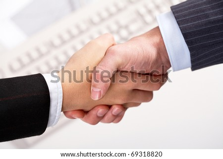 Close-up of partners handshaking over keyboard - stock photo