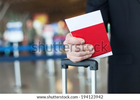 close up of passport and ticket in hand in airport - stock photo