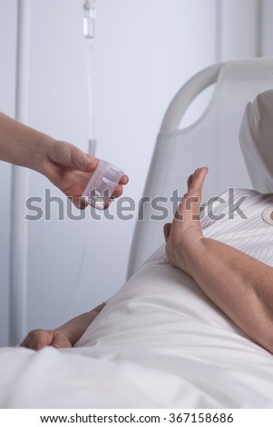 Close-up of patient refusing to take her medication - stock photo