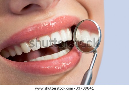 Close-up of patient?s healthy smile with mirror near by