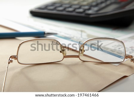 Close-up of pen and calculator on paper - stock photo